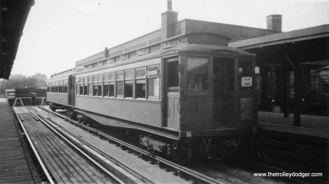 """A two-car train of wooden """"L"""" cars at Logan Square."""