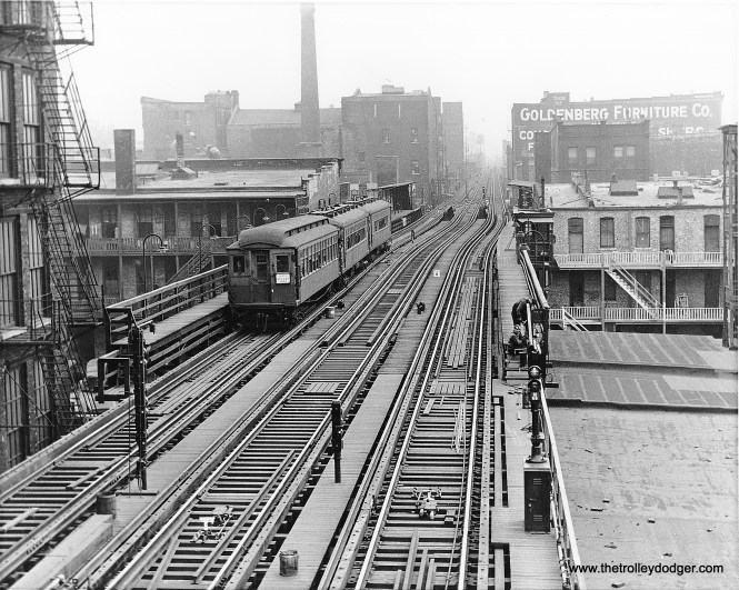"""A northbound midday express train passes the 18th Street """"L"""" station, just prior to the October 1943 opening the State Street Subway. The new signals that controlled access to the subway are already in place. A wooden Pullman-built trailer, built around the turn of the century, is being pushed by two early 1920s 4000-series cars. Once the subway opened, all 455 steel-bodied cars were needed there, and mixed consists such as these became a thing of the past. When the Chicago Transit Authority made a major revision of north-south service in 1949, the third track here was taken out of service, and was eventually removed. (Chicago Transit Authority Historical Collection)"""