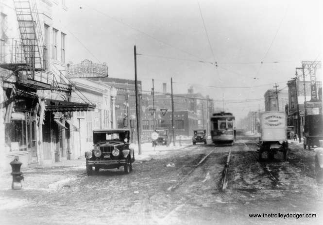"""This one is too fuzzy to see much, except that it is the east end of an east-west streetcar line on the north side, since the tracks end abruptly. I assume that's Broadway crossing on an angle. Miles Beitler, on the other hand, writes: """"I searched the listings for the auto service garage on the right side of the photo. I found a listing for """"Ragalie Bros. Auto Service"""" with a location of 3939 West 5th Avenue, a diagonal street. 3939 is at the intersection of 5th Avenue and Harrison Street. When I checked the 1932 telephone book I found (a) listing for Micheli Restaurant. That location -- 3953 West Harrison -- is also near the intersection of Harrison and 5th Avenue and it does seem to fit the photo. Moreover, I believe there was a streetcar line on 5th Avenue which ended at Harrison. Of course, the expressway was not there in 1932. Also note the horse drawn Bowman Dairy wagon on the right. I believe that Bowman Dairy used horse drawn delivery wagons well into the 1920s."""""""