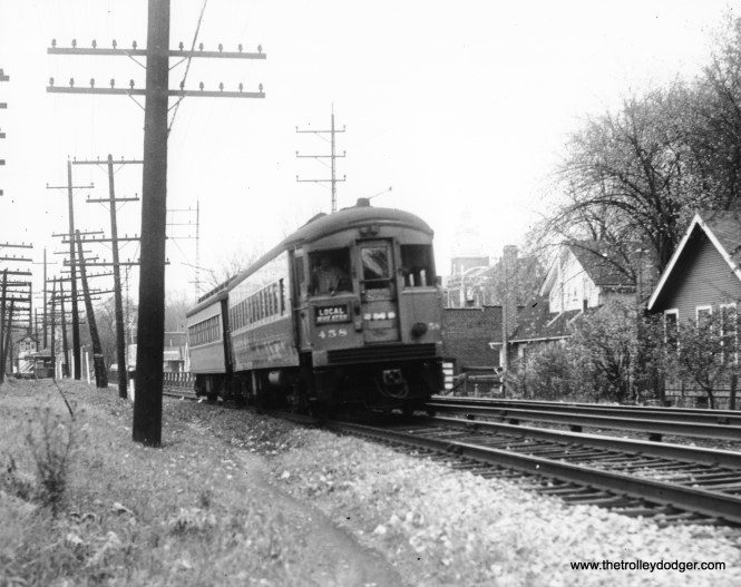 """CA&E 458 heads up a Wheaton local. Not sure where this is. Dann Chamberlin: """"The train has just left the Main Street Glen Ellyn stop headed west towards Wheaton. The Main Street gate tower can be seen in the left-rear of the photo. To the right of 458 one can make out the tower of today's Glen Ellyn Civic Center. I attended junior high school in that building!"""""""