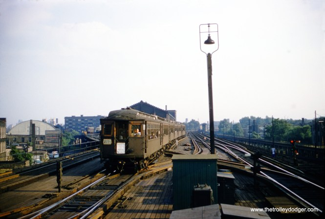 A 6-car Evanston Express train, made up of wood-steel cars, heads northbound approaching the Wilson Avenue station in August 1957. The Wilson Shops is in the background behind the train. At right, you can see the ramp that went down to Buena Yard.