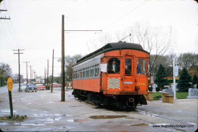 """CA&E 318 is on a mid-1950s fantrip sponsored by the Illini Railroad Club. The car is out on the Mount Carmel branch. You can see Maury Klebolt (1930-1988), the trip organizer, in the window. Mike Franklin: """"This photo is looking west on the north side of Roosevelt Rd in Hillside taken from Oak Ridge Ave. That is not a cemetery on the right but rather the outdoor show room for Peter Troost Monument Co, same as today. Queen of Heaven Mausoleum at Wolf & Roosevelt can be seen in the distant left."""""""