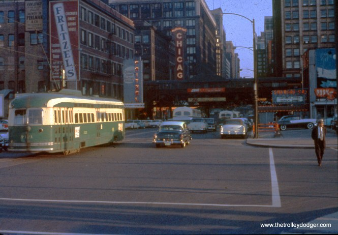 """CTA PCC 7171 heads south on State Street at Wacker Drive, most likely on Route 36. The CTA """"L"""" station at State and Lake Streets is a block away, with Fritzel's restaurant and the Chicago Theater visible. This picture dates to the mid-1950s."""