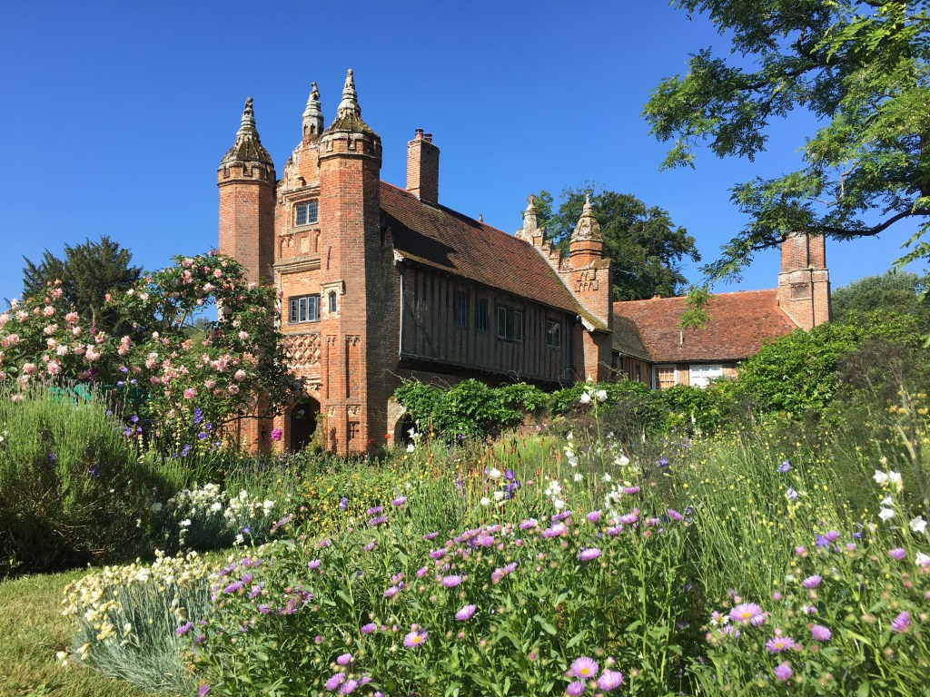 A picture of a Tudor gatehouse set in and English garden.