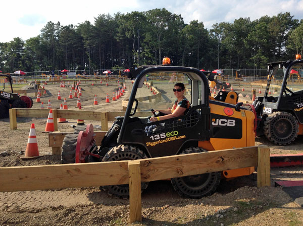Shannon driving a skid steer.
