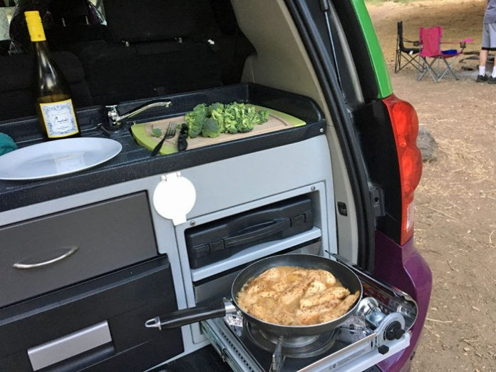 Cooking chicken & broccoli in the JUCY campervan kitchen.