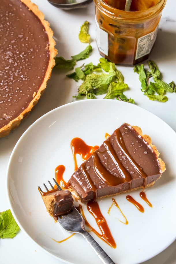 Rich and decadent milk chocolate tart slice on a white plate.