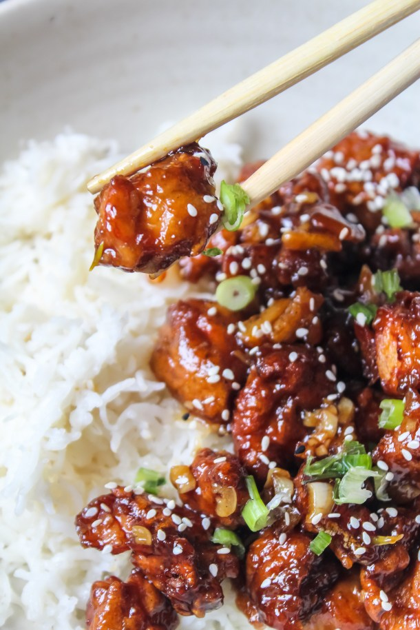 Crispy Fried Chinese Orange Chicken topped with spring onions, placed in a white bowl with rice.
