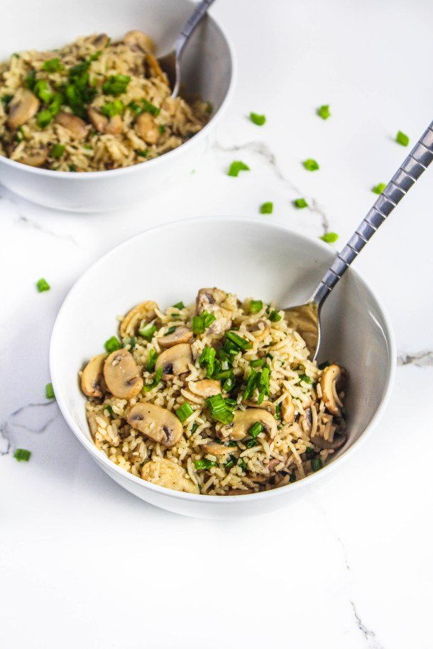 Garlic butter mushroom rice tossed in spring onions in white bowl on a white surface