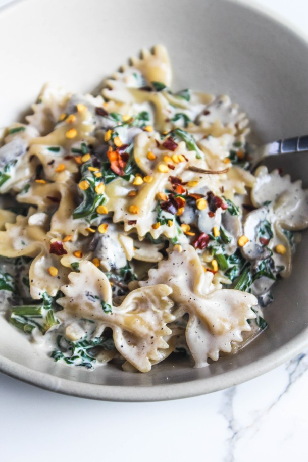 Creamy Mushroom and Spinach Pasta with red pepper flakes in a white bowl on a white tile
