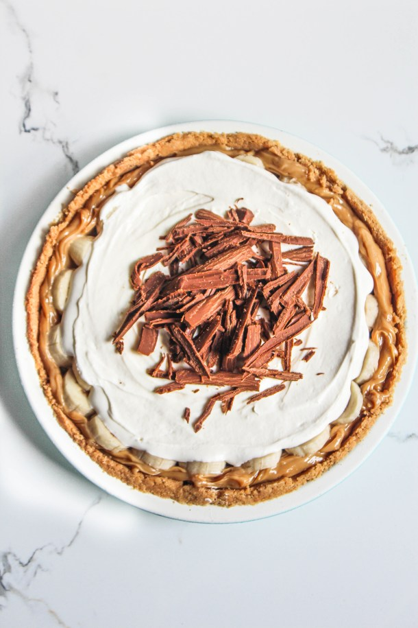 Brown and white color banoffee pie with cream, bananas and dulce de leche on a white plate over a white tile.
