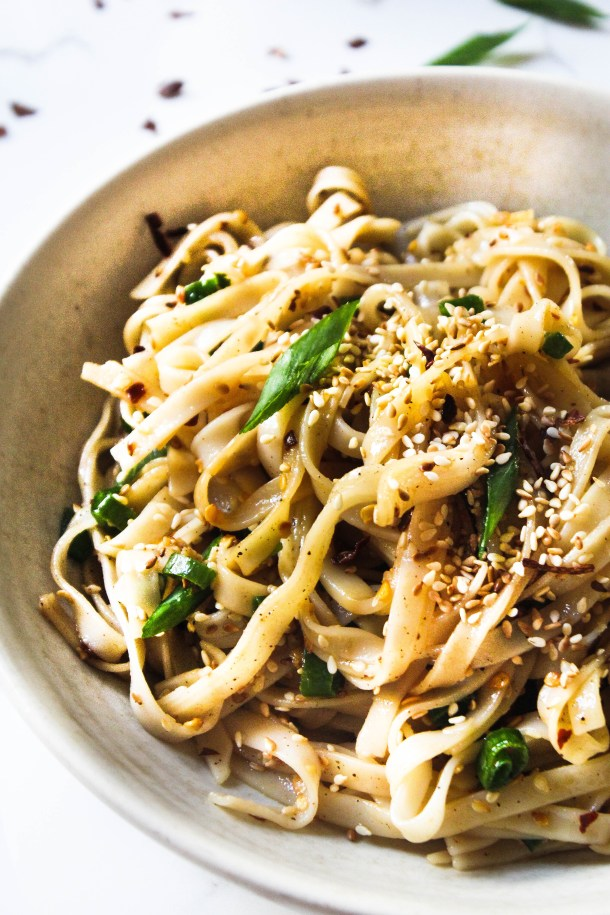 yellow flat rice noodles tossed in soy sauce, sesame oil and vinegar. Topped with green spring onions, toasted brown sesame seeds. Over a white bowl placed on a white tile.