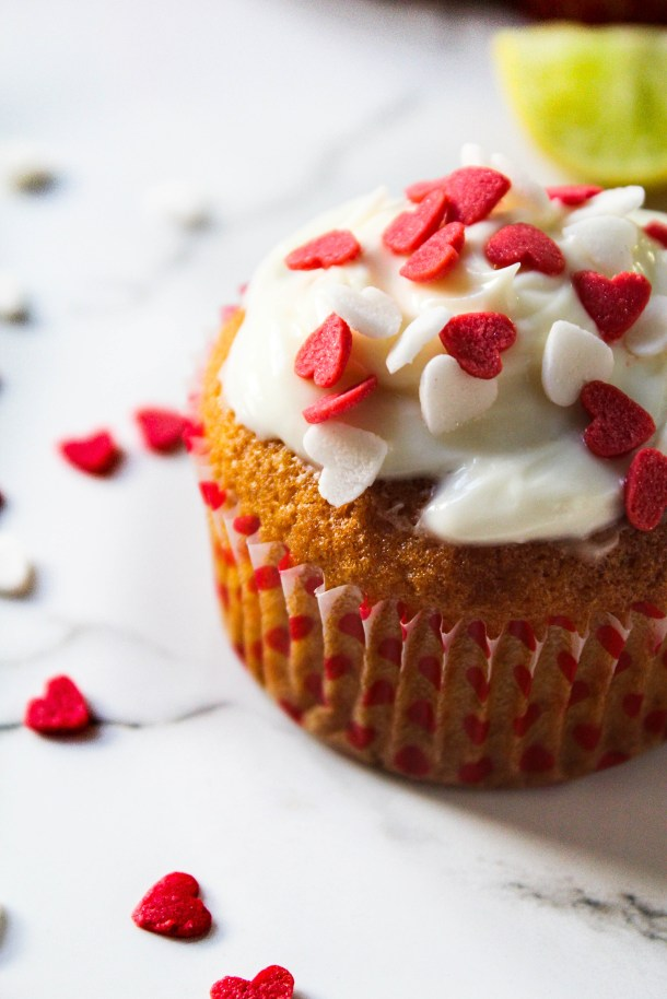 Yellow Lemon cupcakes topped with white cream cheese frosting and red and white heart shaped sprinkles perfect for valentines dessert