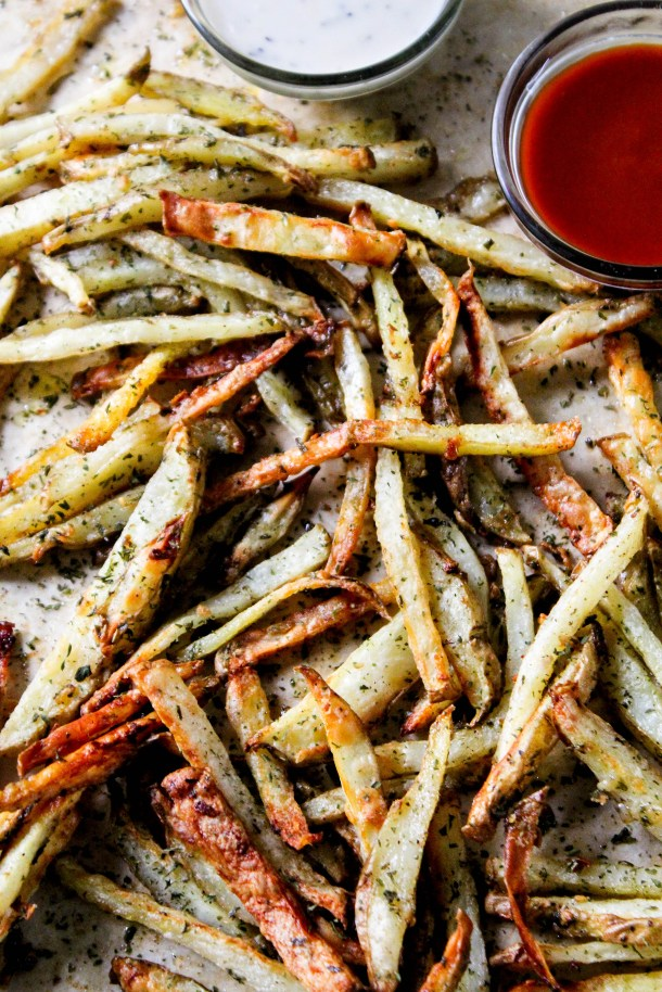 Golden thin cut brown crunchy and crispy potato french fries that are baked and tossed in garlic butter with green dried parsley served on a brown sheet on baking tray with red ketchup and white dip.