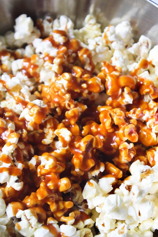 White puffed and popped pop corn in a bowl on a white tile. topped with homemade salted caramel sauce.