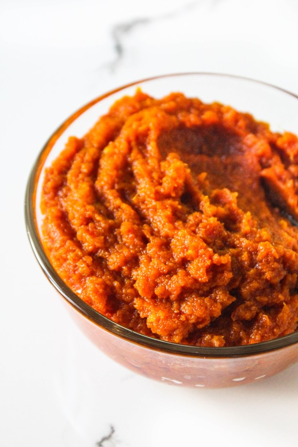 Thick Red Indian curry paste (bhuna masala) in a glass bowl on a white tile.