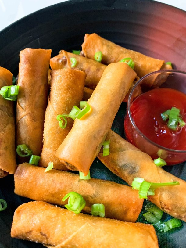 golden fried spring rolls filled with vegetables served in a black plate placed on a white tile