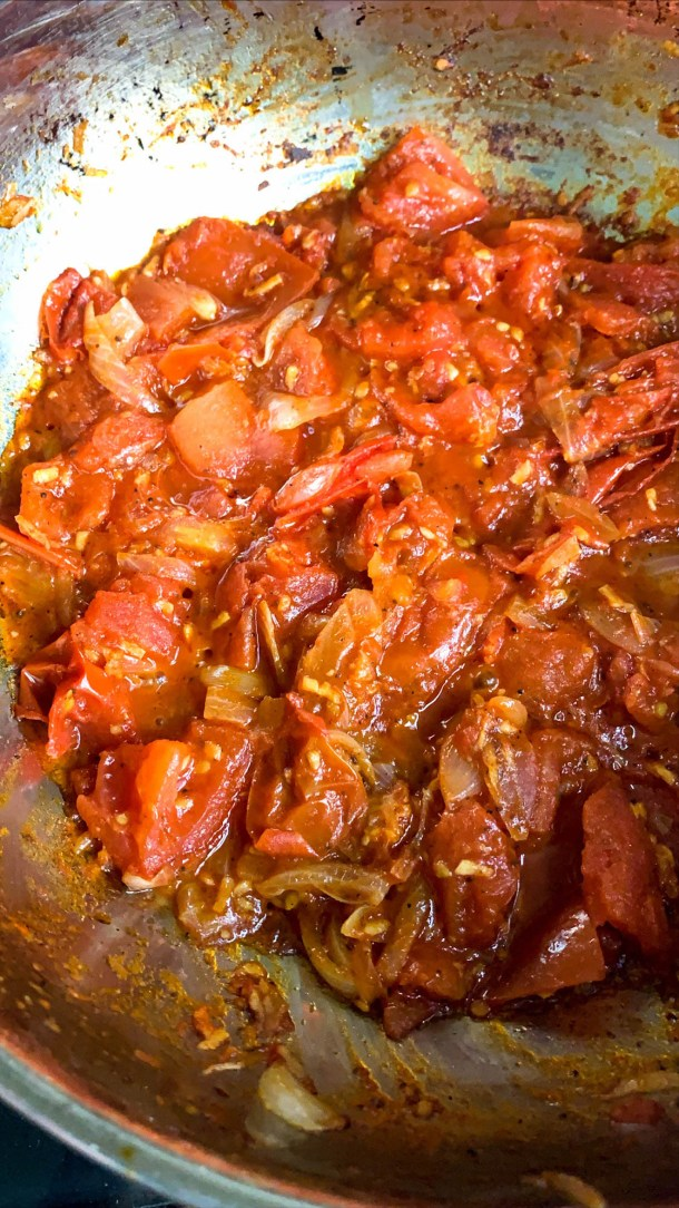 Onions and tomatoes sautéed in a pan.