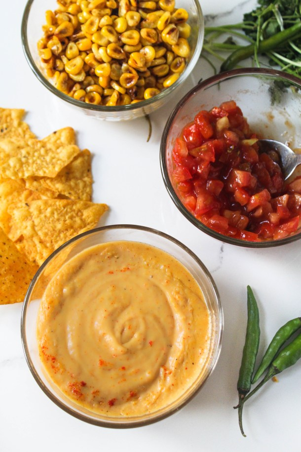 Nachos loaded with homemade orange cheddar cheese sauce, tomatoes, grilled corn, olives, topped with green coriander - served on a baking sheet and placed on a white tile.