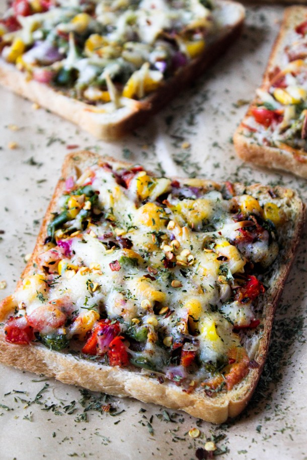 Toasted white bread topped with onions, tomatoes, sweet corn, capsicum and mozzarella and cheddar cheese, placed on a brown paper