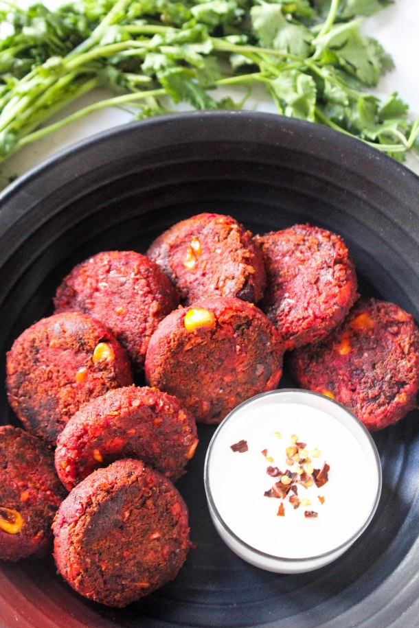 Soft Gluten Free Beetroot, Corn, Carrots and Chickpea Kebabs in a black dish served with a white dip - placed over a white tile with coriander as garnish