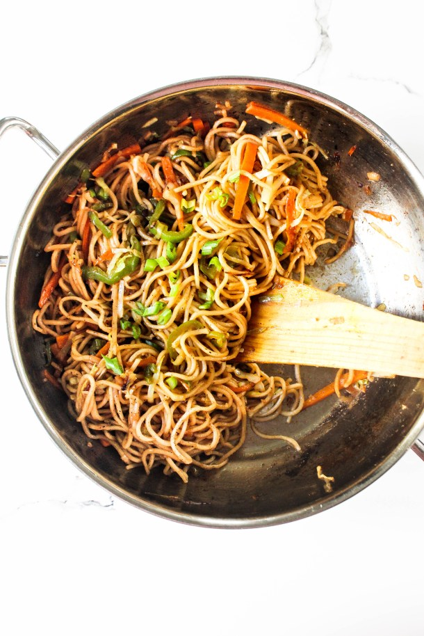 Hakka noodles in a wok placed on a white tile.