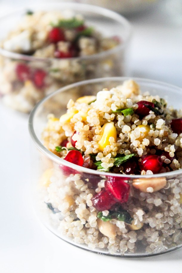 Quinoa salad with corn, pomegranate, peanuts, fresh mint leaves, paneer (indian cottage cheese) in a glass bowl.