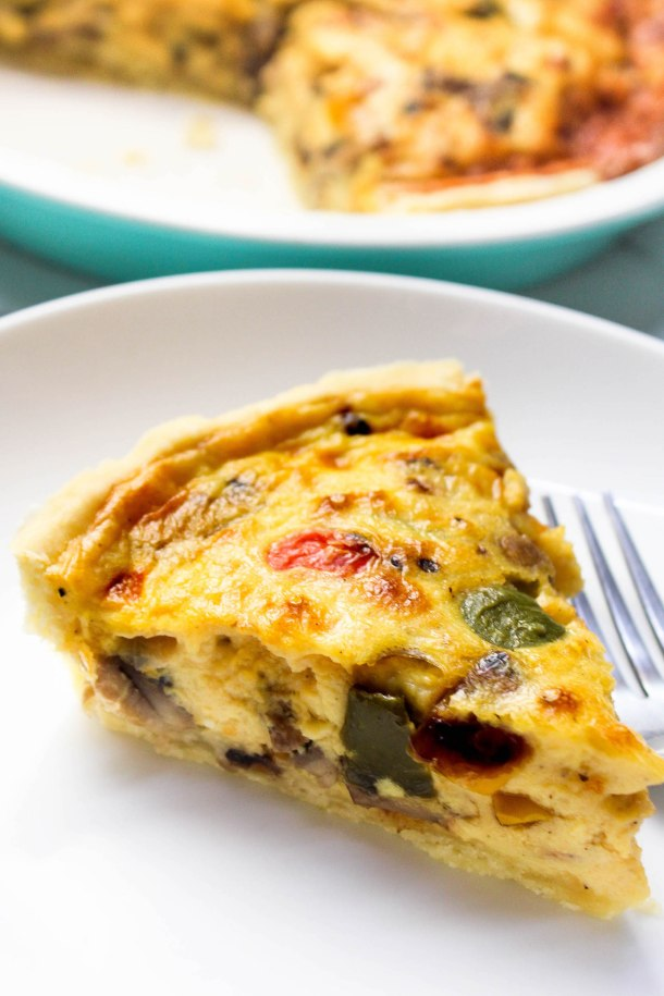 Homemade vegetarian quiche with mushrooms, peppers and onions on a white plate.