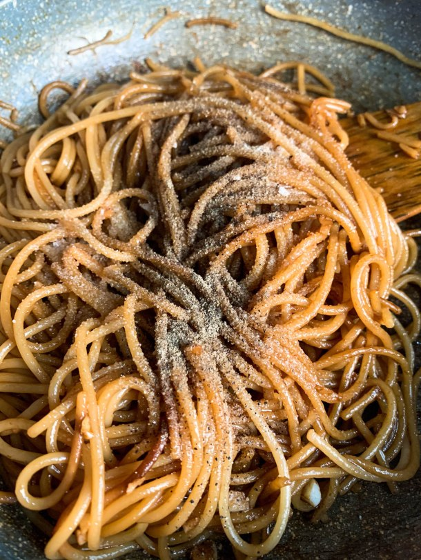 Spaghetti noodles tossed in asian sweet and spicy sauce topped with salt and pepper - in a pan.