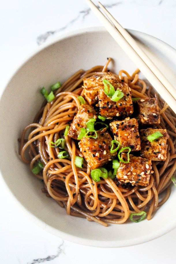 Brown asian style sweet and spicy spaghetti noodles topped with crunchy oven baked tofu - served in a white serving bowl and topped with spring onions and sesame seeds.