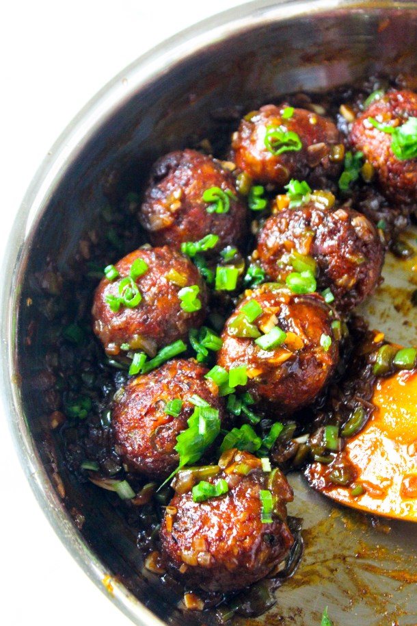 Brown sticky asian chinese vegetatian manchurian meatless meatballs topped with spring onions in a large pan.