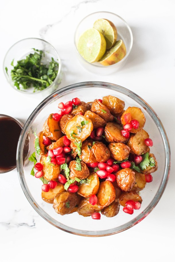Healthy Baked aaloo chaat in a glass bowl. Crunchy baked baby Potatoes tossed with red pomegranate and sweet sauce.