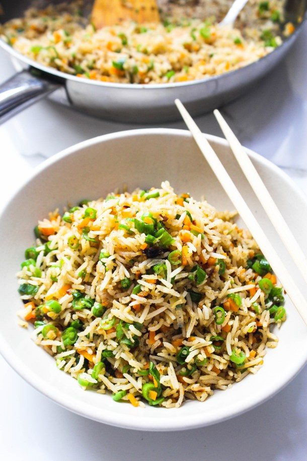 Ginger Garlic Fried Rice with Vegetables in a large bowl with chopsticks placed on a white tile.