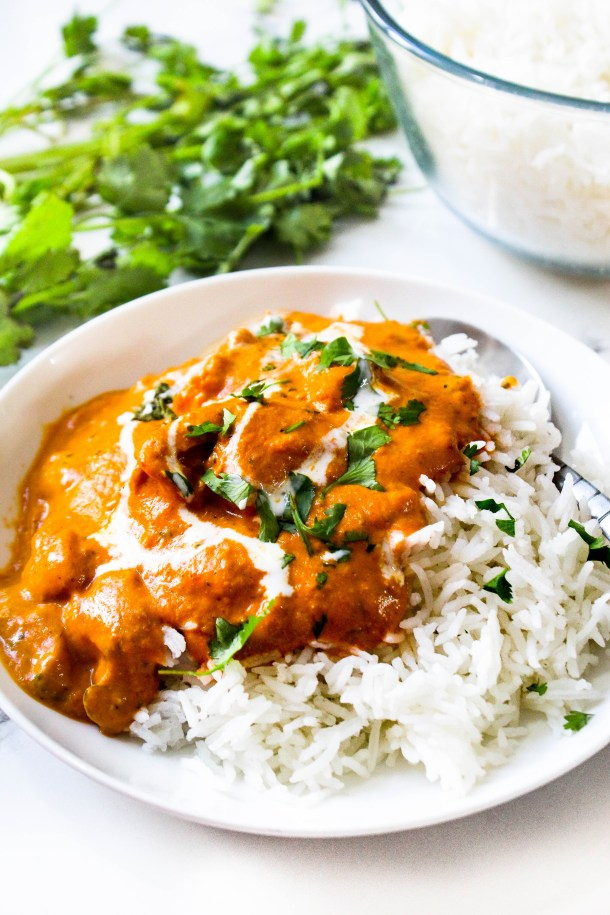 Butter Chicken in a bowl, served over rice. Coriander in background.