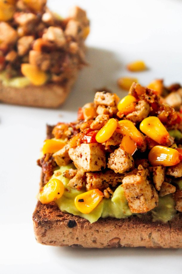 Chipotle tofu scramble on toasted bread with some smashed avocado
