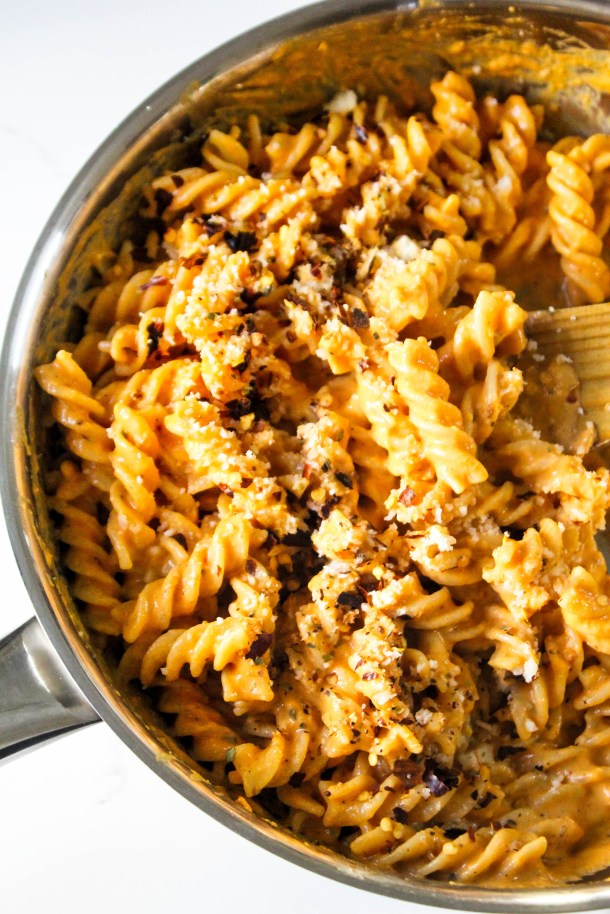 Creamy roasted red pepper fusilli pasta in a frying pan placed on a white tile.