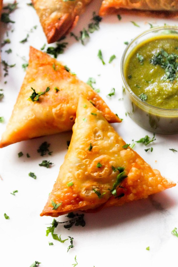 Crunchy bite sized mini samosas filled with sweet potato and peas, placed on a white tile served with green coriander chutney in a small glass bowl