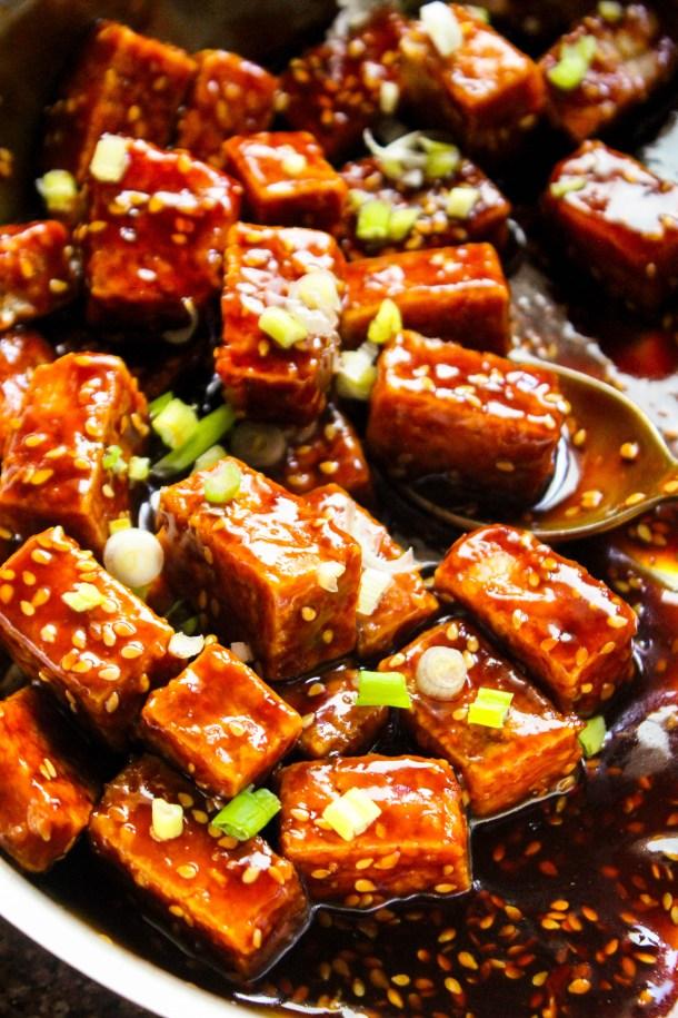 Reddish Brown Sticky Sesame Crispy Tofu served in a pan
