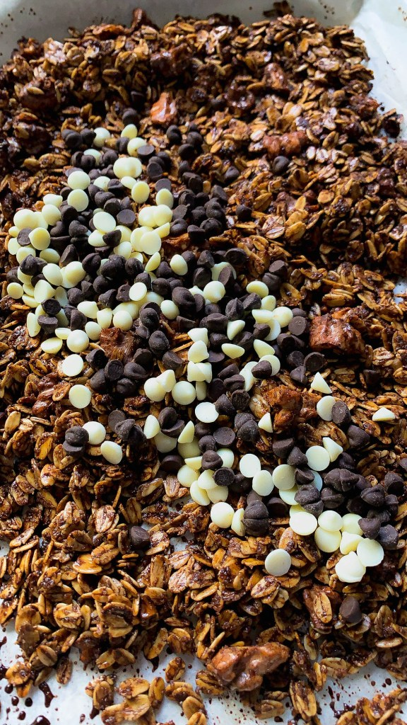 Crunchy homemade chocolate and walnut granola with chocolate chips (white and dark) on them.