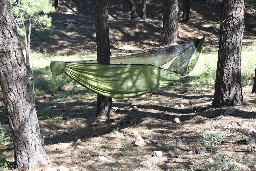"This image shows the foot end of the hammock. Notice that the ""pull out"" point is closer to the end of the hammock, pulling the extra fabric around at the feet instead of near the knee."