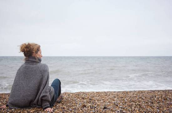 How Natalie learned she has an allergy to cold (Cold Urticaria) and has adapted her life to be able to cope with it better.  Woman sitting on a cold,rocky beach wearing a sweater.