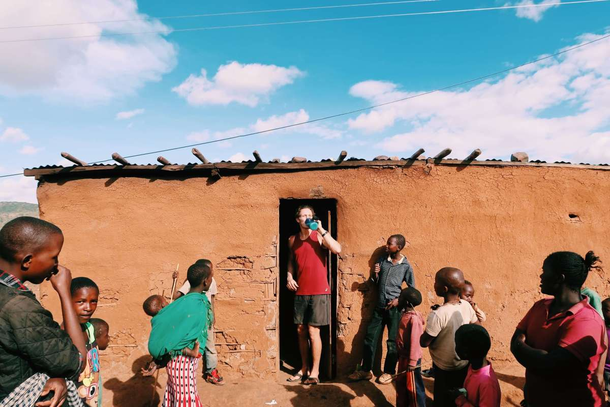 Chris emerging from a hut with Maasai wine surrounded by curious locals