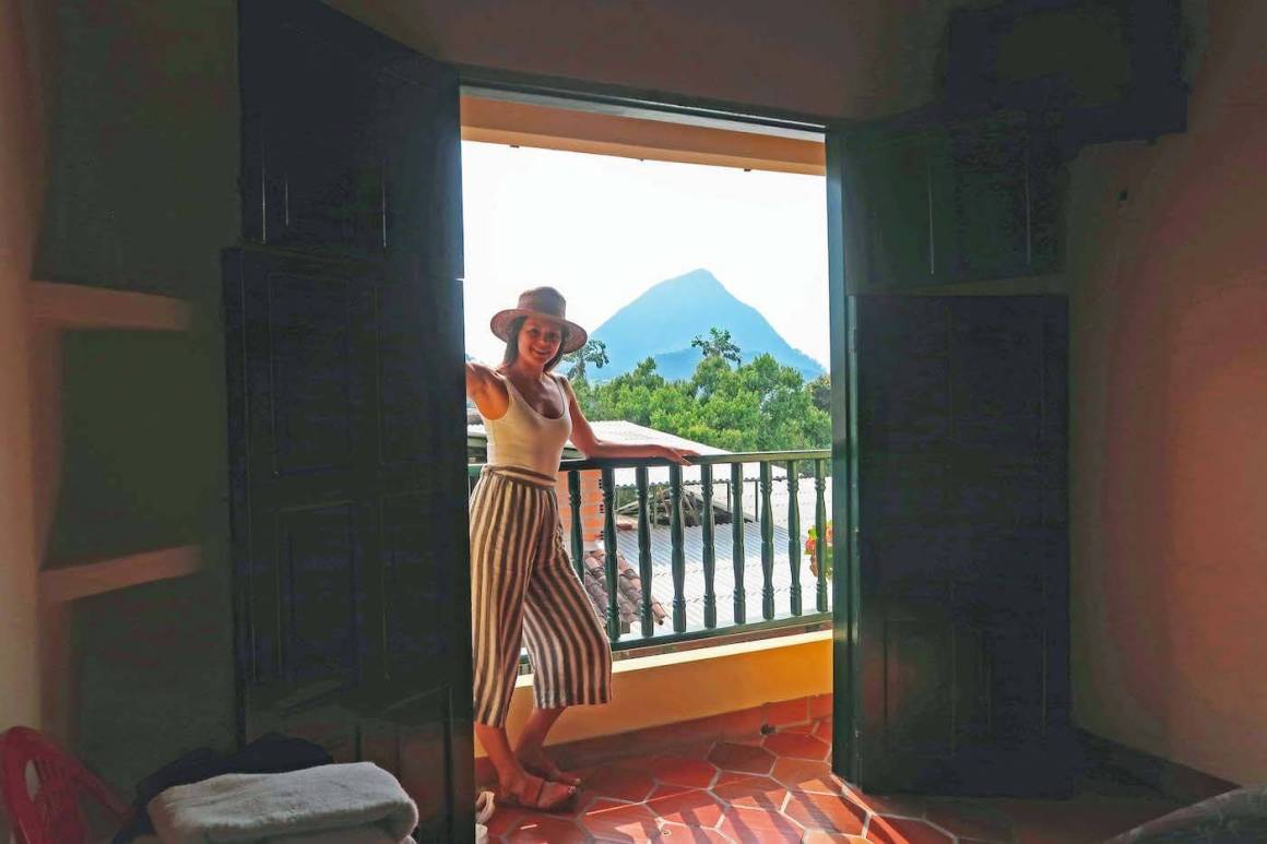 Kim standing by patio of our room in Hotel la Vereda with Cerro Tusa in background