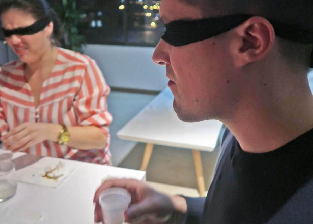 Close up of Austin tasting aguardiente with disgusted Caroline in background