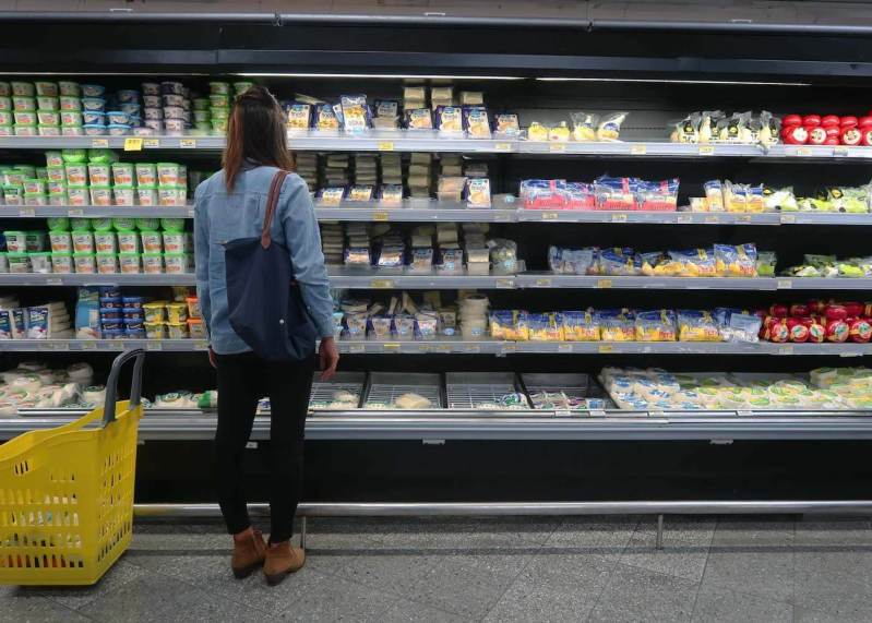Kim staring at all the Colombian cheseses in the Medellin supermarket