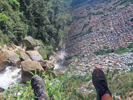 Split screen of feet by waterfall and feet while paragliding in Medellin