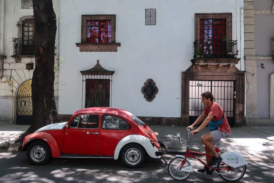 Chris riding EcoBici past a beetle in a Mexico City street