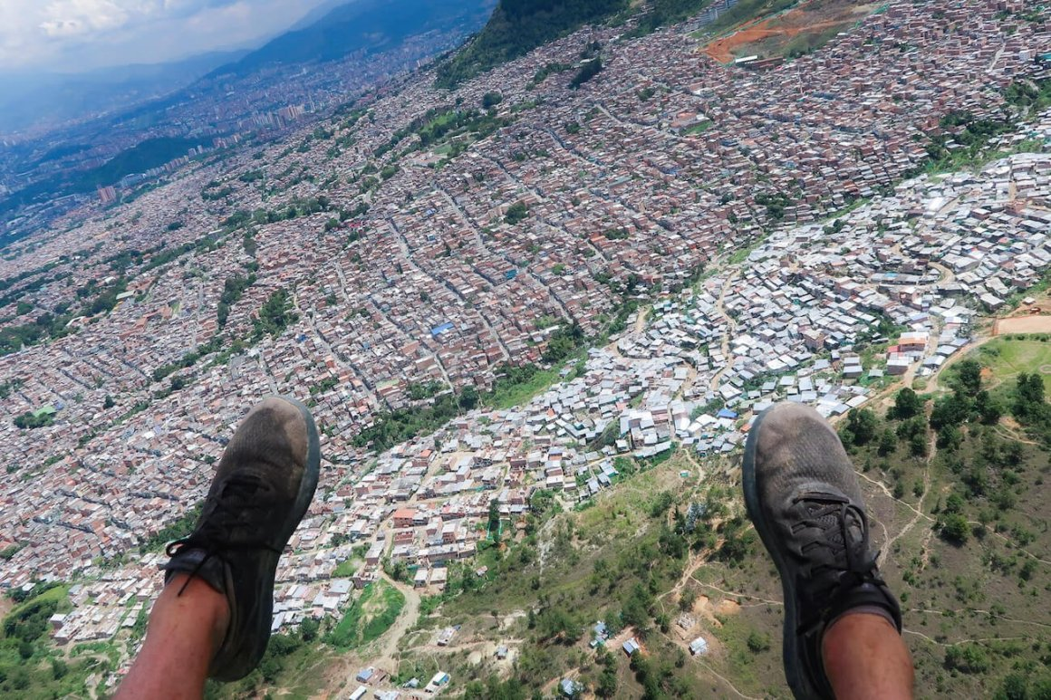 My feet and the view of the city while paragliding in Medellin