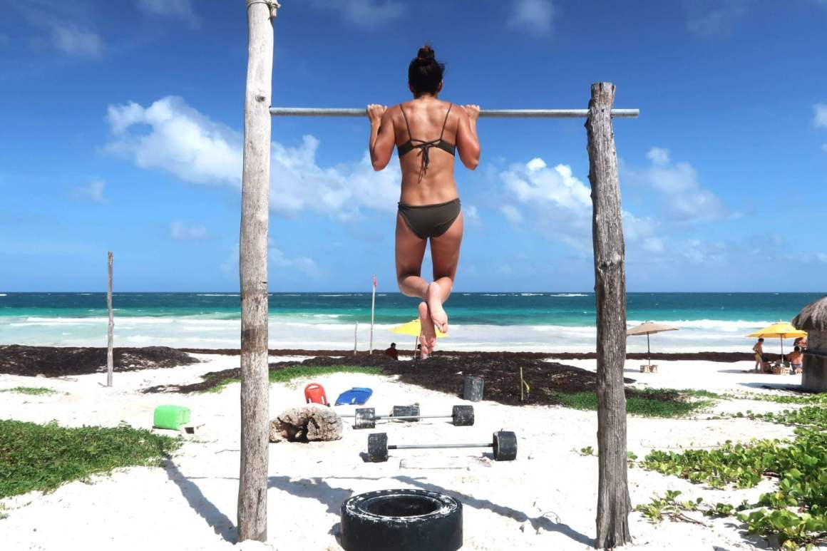 Kim getting in a set of pull-ups at the free outdoor gym in Tulum Mexico
