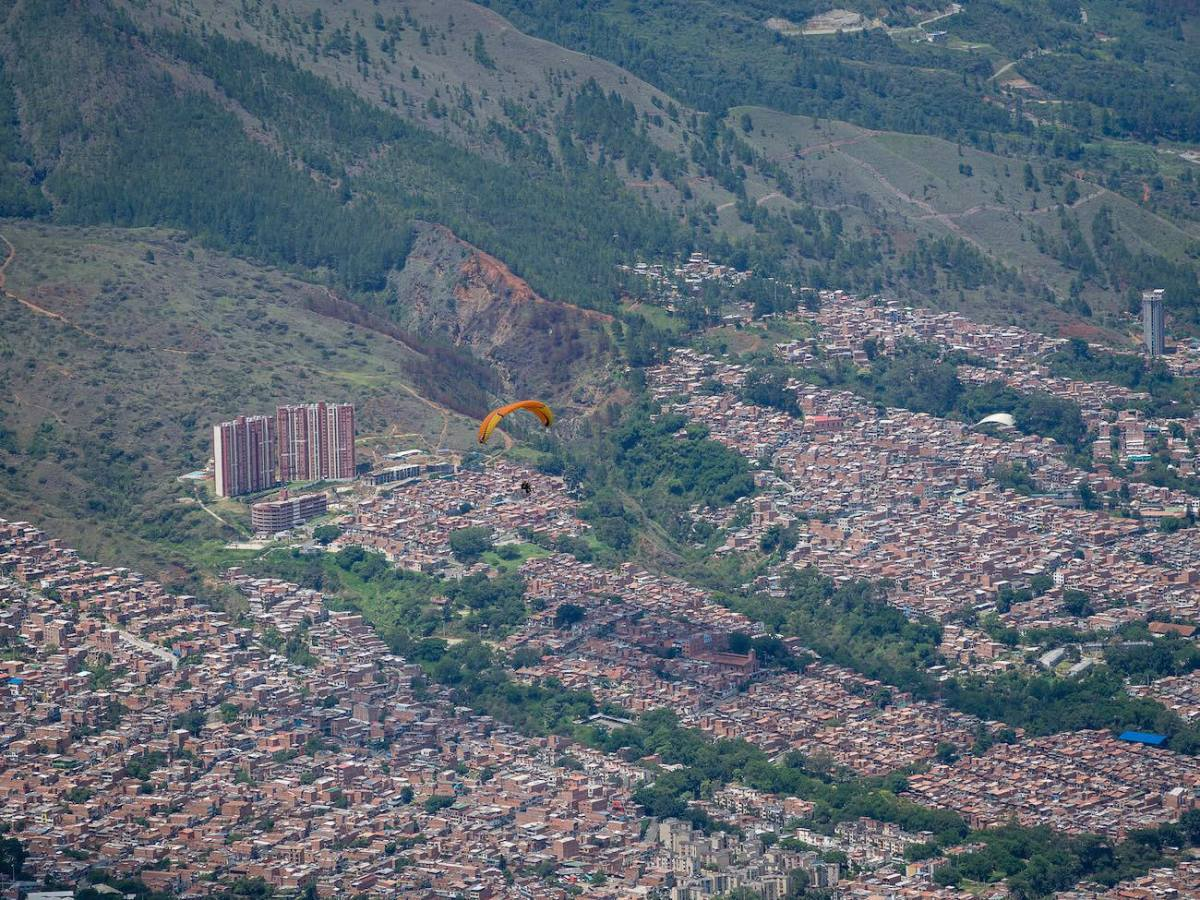 Paraglider in sky with city below